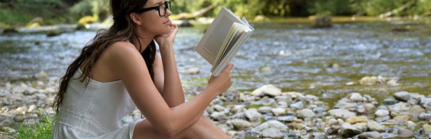 girl reading book by river for wellness